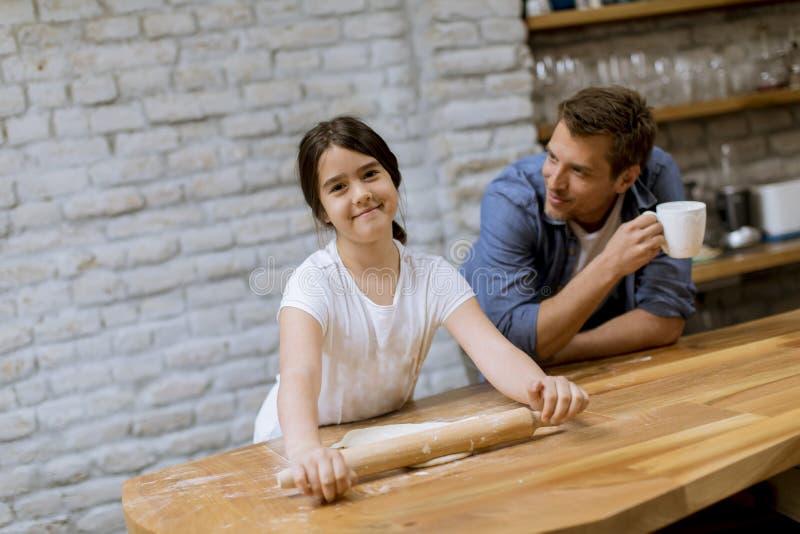Fader och dotter som g?r br?d i k?ket royaltyfria bilder