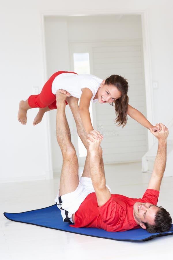 Fader och dotter som gör yogaelevatorn royaltyfri fotografi
