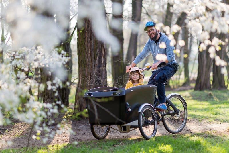 Fader och dotter som har en ritt med lastcykeln arkivbilder