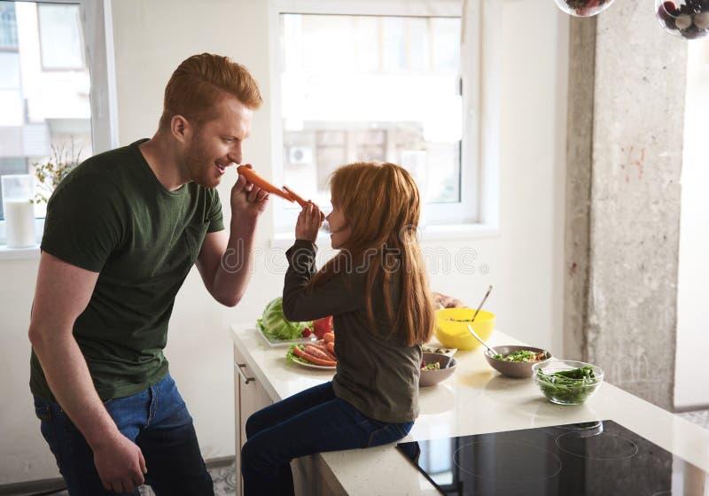 Fader och dotter som har gyckel i kök royaltyfri foto