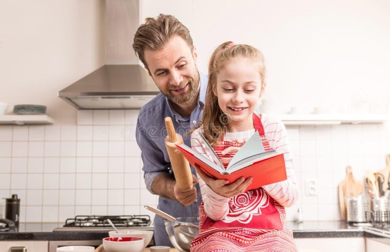 Fader och dotter som har gyckel i köket - baka royaltyfria bilder