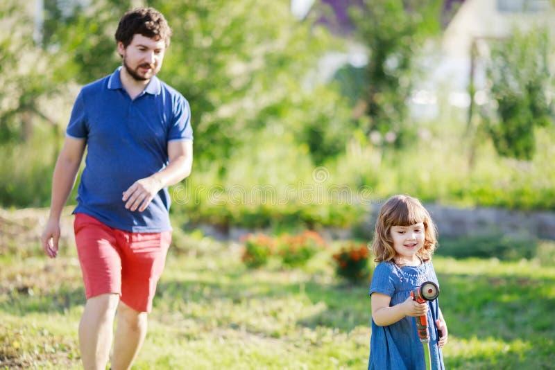 Fader och dotter som har gyckel i trädgården som bevattnar växter royaltyfri foto