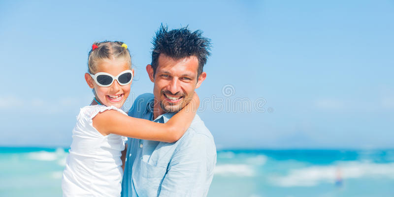 Fader och dotter som har gyckel på strand royaltyfri bild