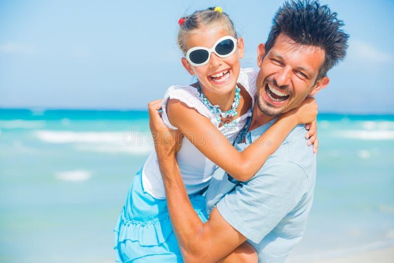 Fader och dotter som har gyckel på strand royaltyfri foto