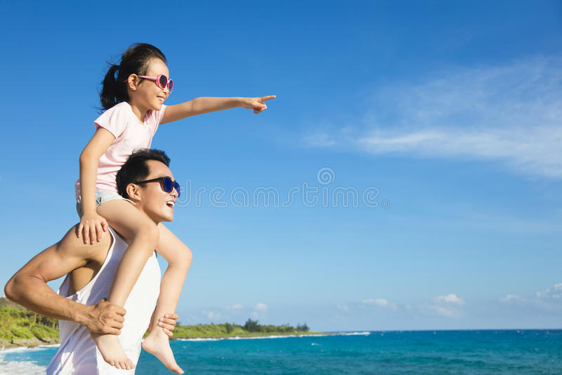 Fader och dotter som har gyckel på stranden arkivbilder
