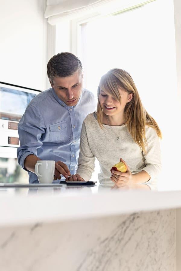 Fader och dotter som hemma använder minnestavlaPC arkivfoto