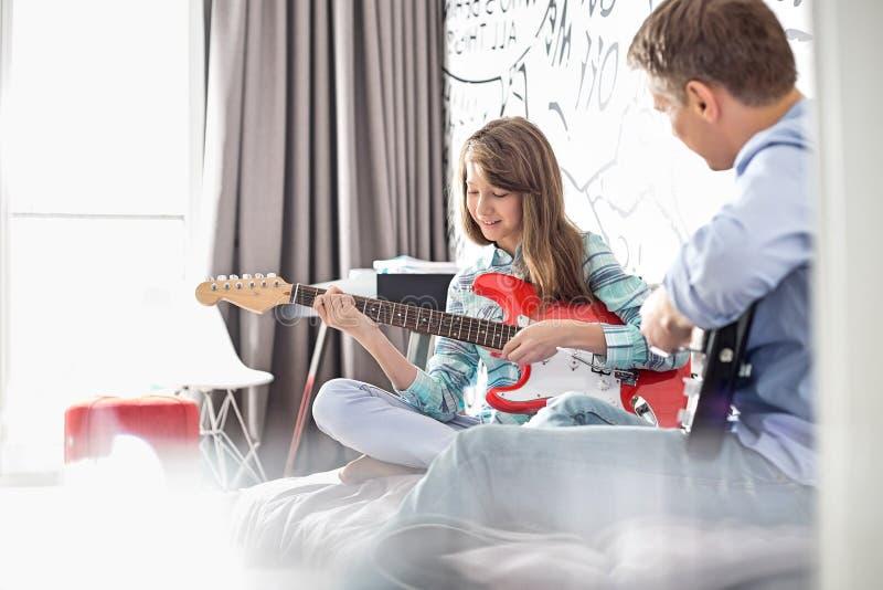 Fader och dotter som hemma spelar elektriska gitarrer arkivbild