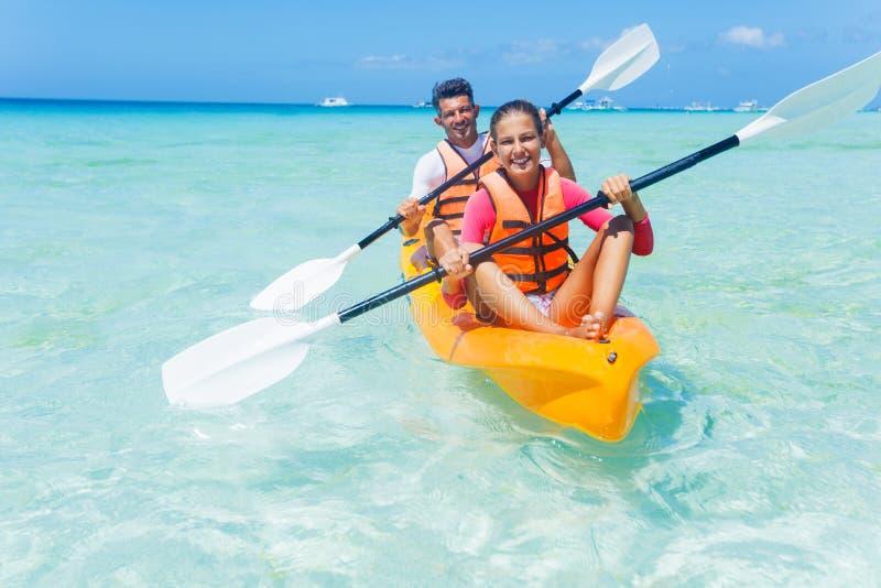 Fader och dotter som kayaking på det tropiska havet arkivfoto