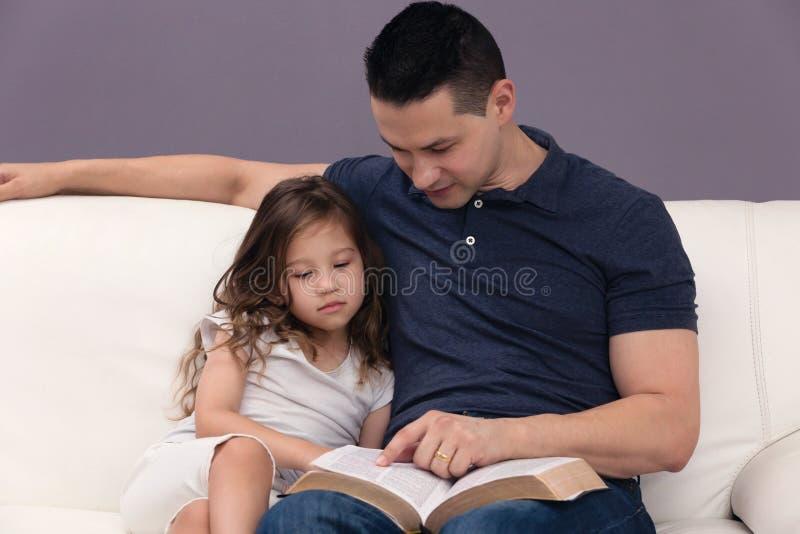 Fader och dotter som läser bibeln arkivfoto