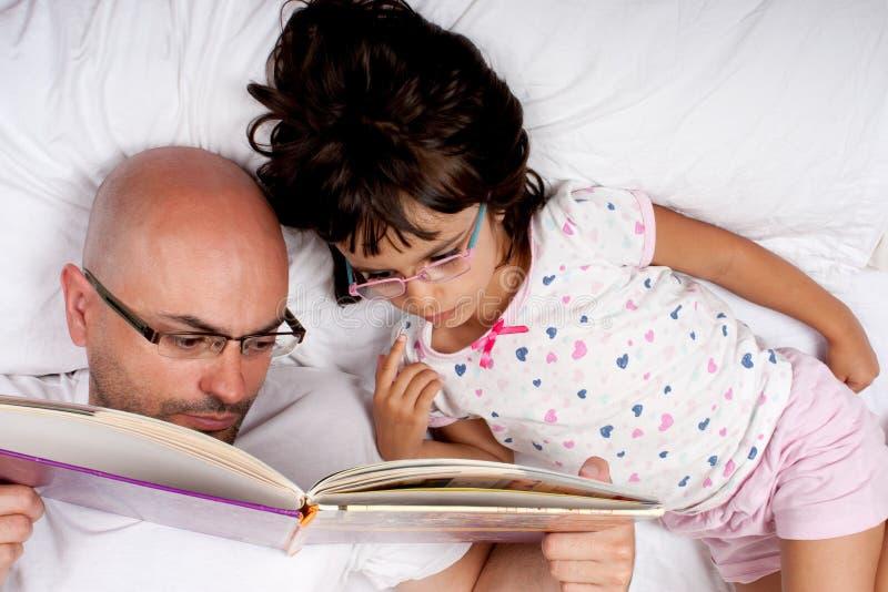 Fader och dotter som läser en bok i underlag arkivfoto