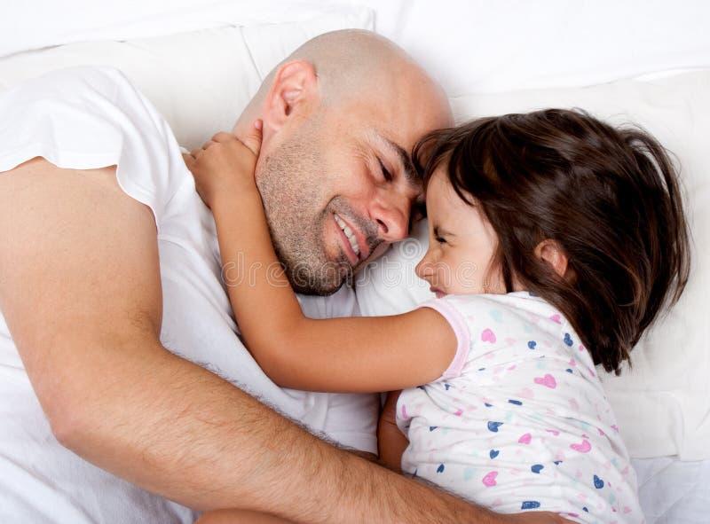 Fader och dotter som leker i underlag i morgonen royaltyfria foton