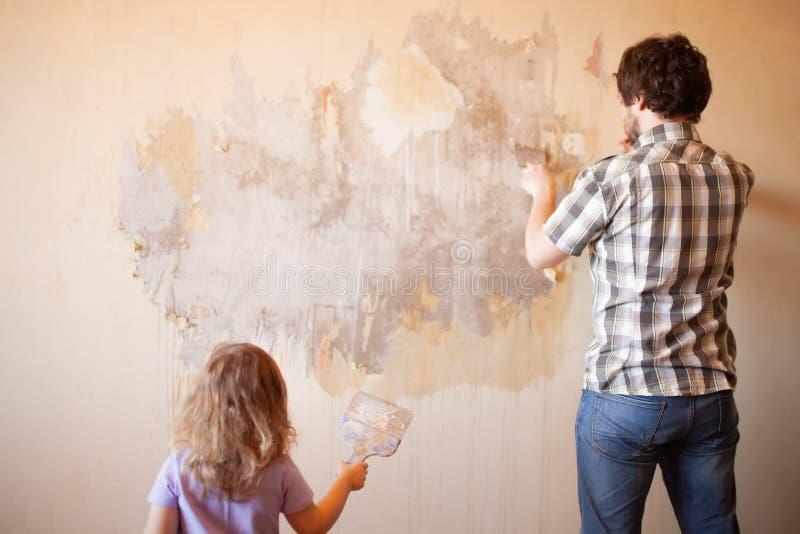 Fader och dotter som reparerar väggen som rymmer spackeln arkivfoton
