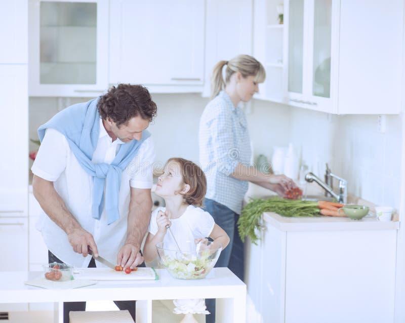 Fader och dotter som ser de stund som förbereder sunt mål i kök royaltyfri foto