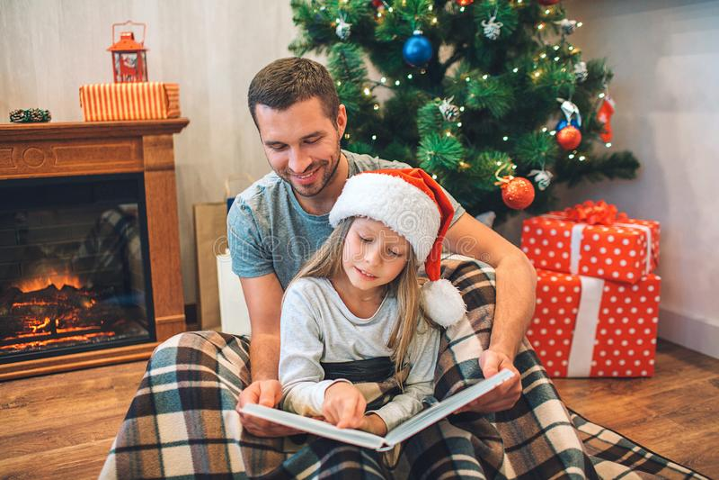 Fader och dotter som sitter på golv på filten och läseboken De håller det öppnat mannen ler barn Flickan är lugna royaltyfri foto