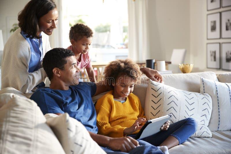 Fader och dotter som sitter på soffan genom att använda minnestavladatoren, modern och litet barnsonen som lutar bak dem, låg vin royaltyfria bilder