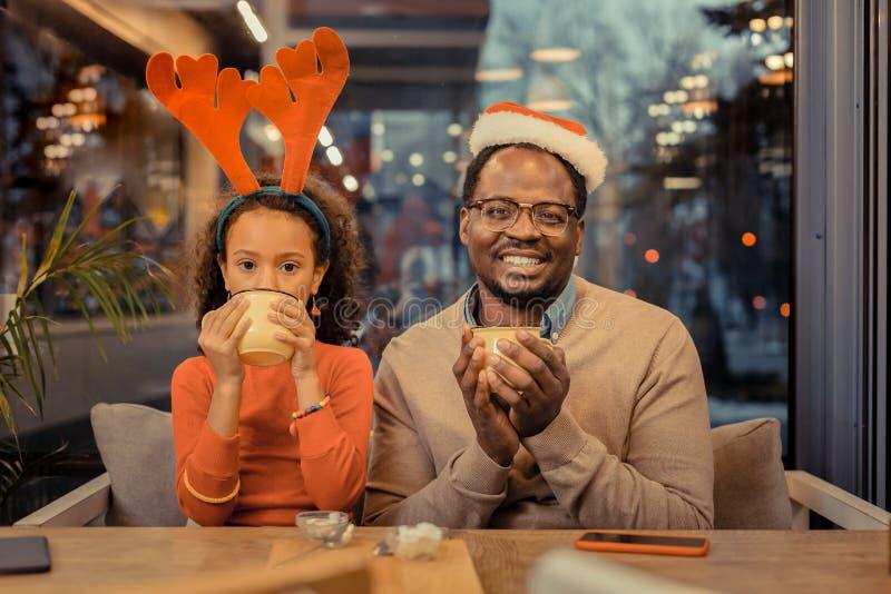 Fader och dotter som sitter på tabellen i kafeteria på juldag royaltyfri fotografi