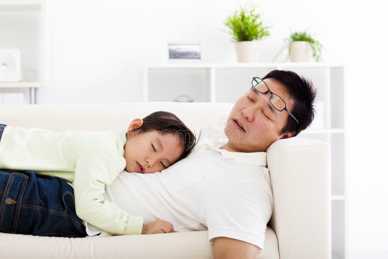 Fader och dotter som sover på soffan royaltyfri bild