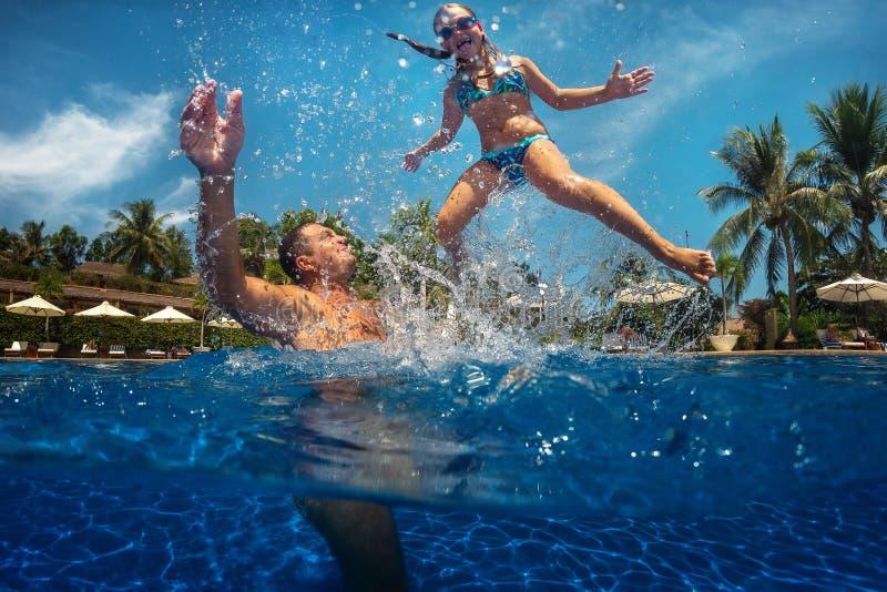 Fader och dotter som spelar i en simbassäng arkivfoton