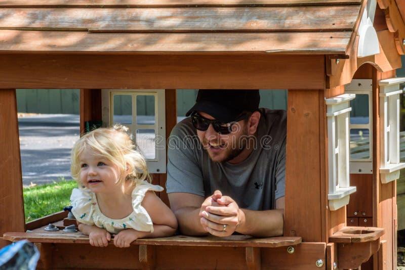 Fader och dotter som spelar i lekstuga i trädgård royaltyfri foto