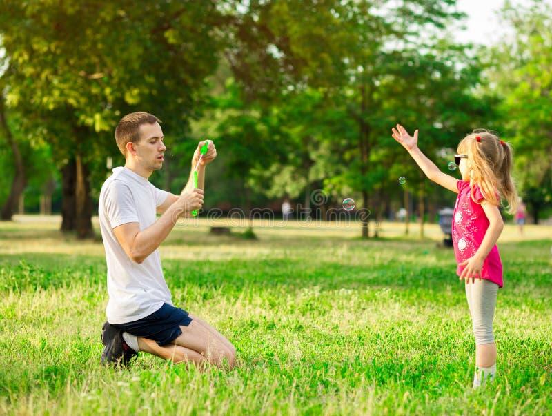 Fader och dotter som spelar i parkera p? dagtiden Begrepp av familjen arkivfoto