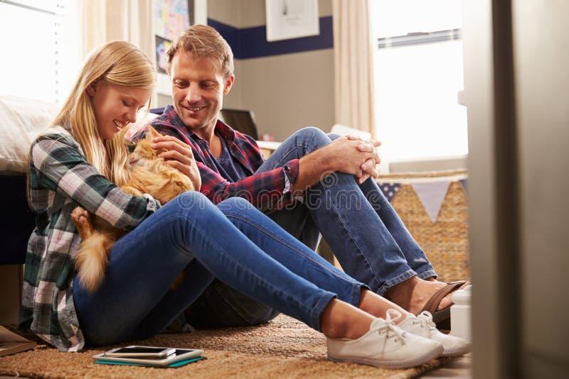 Fader och dotter som spelar med den älsklings- katten royaltyfri fotografi