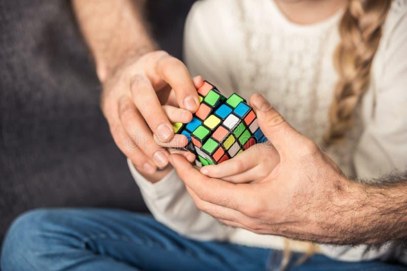 Fader och dotter som spelar med kuben royaltyfri bild
