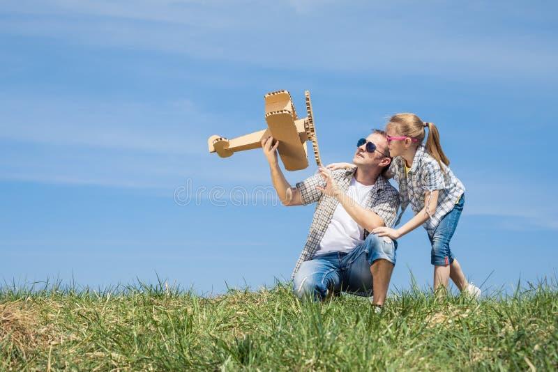 Fader och dotter som spelar med pappleksakflygplanet i pet royaltyfria bilder