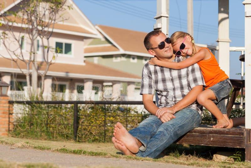 Fader och dotter som spelar nära huset på dagtiden arkivfoton