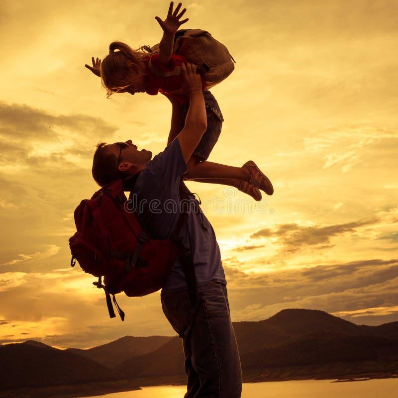Fader och dotter som spelar på kusten av sjön på solnedgången t arkivfoto
