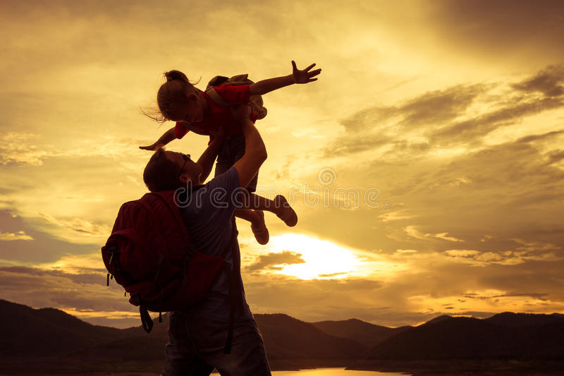 Fader och dotter som spelar på kusten av sjön på solnedgången t fotografering för bildbyråer