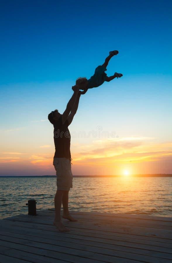 Fader och dotter som spelar på pir royaltyfria foton