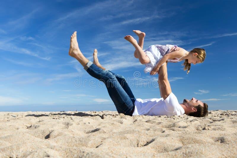 Fader och dotter som spelar på stranden royaltyfri fotografi