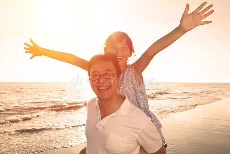 Fader och dotter som spelar på stranden arkivfoto