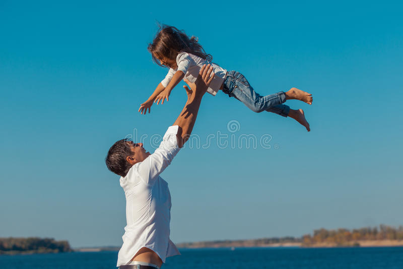 Fader och dotter som spelar på stranden på dagen arkivfoto