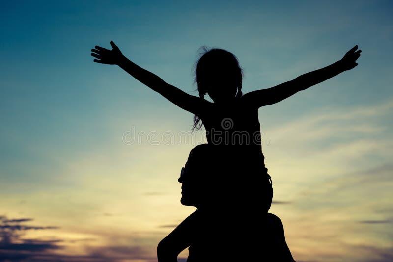 Fader och dotter som spelar på stranden på solnedgångtiden arkivfoto