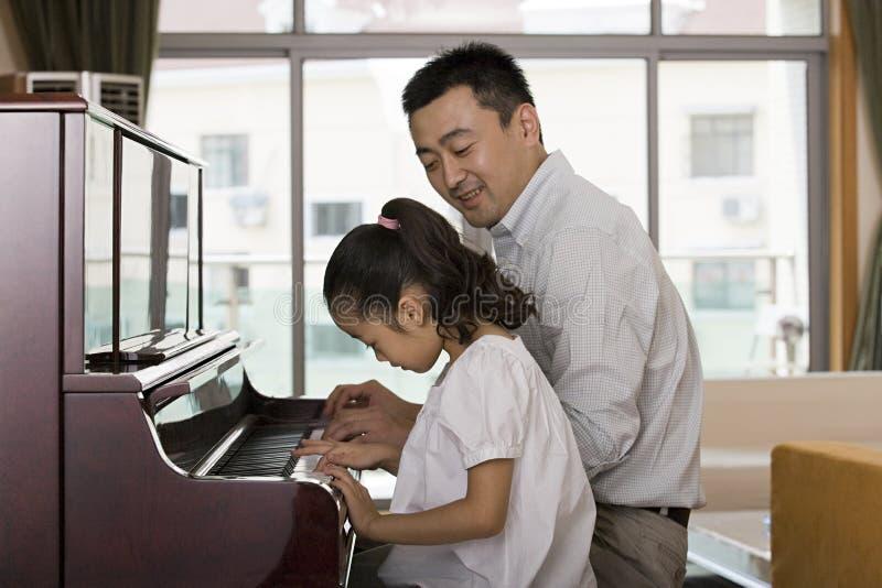 Fader och dotter som spelar pianot royaltyfri foto