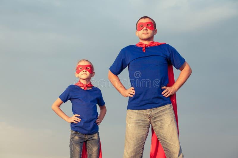 Fader och dotter som spelar superheroen på dagtiden royaltyfri foto