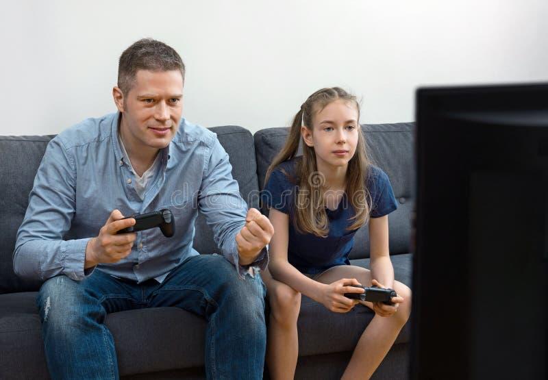 Fader och dotter som spelar videospelet arkivfoto