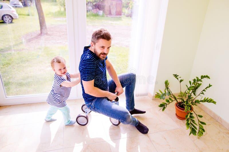 Fader och dotter som tillsammans spelar och att rida en cykel inomhus arkivbilder