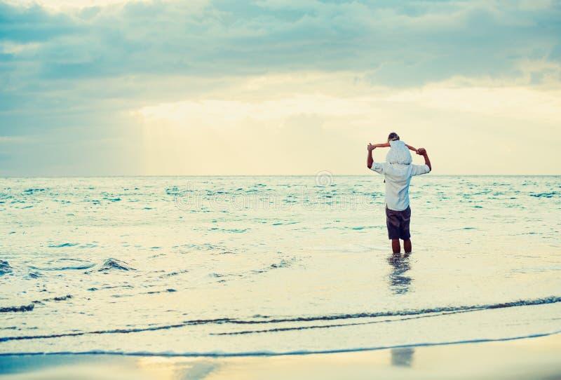 Fader och dotter som tillsammans spelar på stranden på solnedgången fotografering för bildbyråer