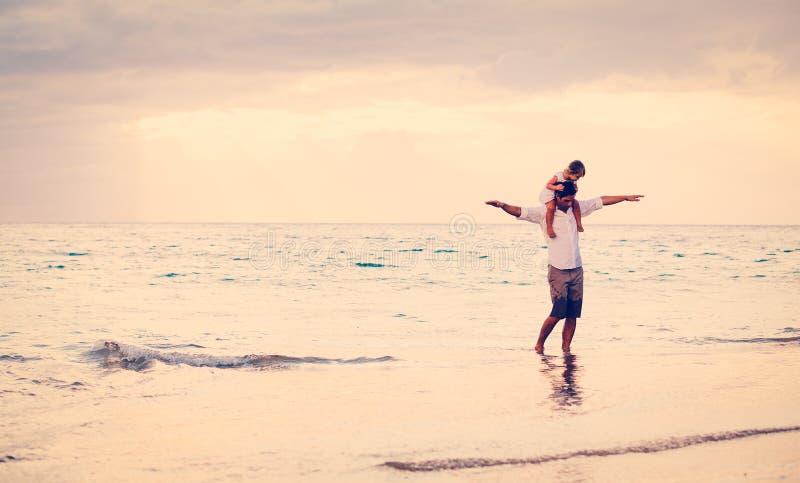 Fader och dotter som tillsammans spelar på stranden på solnedgången arkivfoton