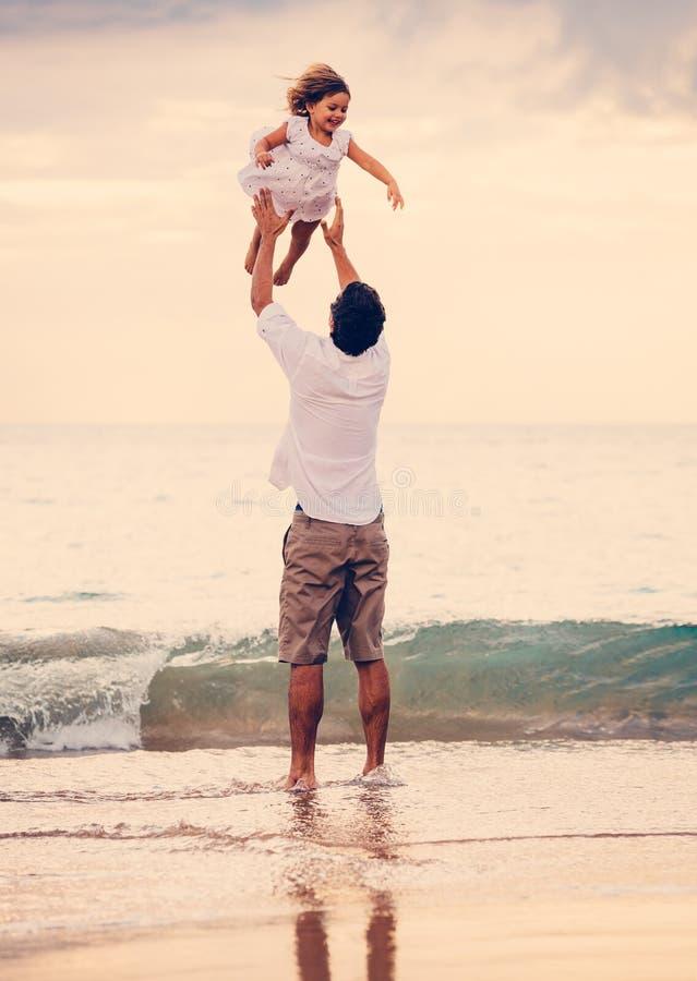 Fader och dotter som tillsammans spelar på stranden på solnedgången royaltyfri foto