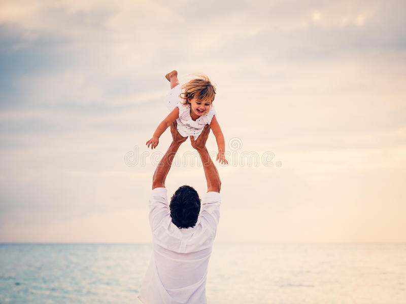 Fader och dotter som tillsammans spelar på stranden på solnedgången royaltyfria bilder