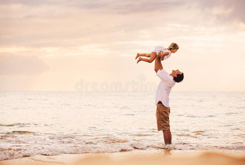 Fader och dotter som tillsammans spelar på stranden på solnedgången royaltyfria foton