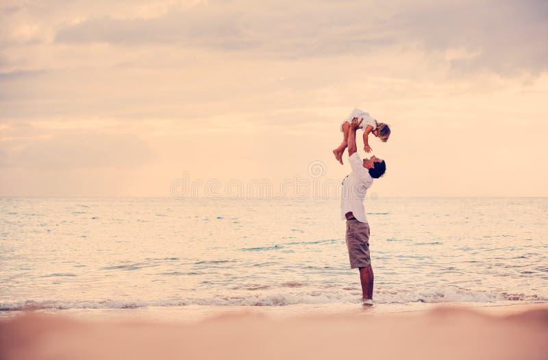 Fader och dotter som tillsammans spelar på stranden på solnedgången royaltyfri fotografi