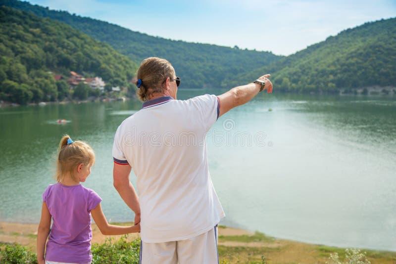 Fader- och dotteranseende på kusten av sjön och rymmahänderna Fadern visar en hand framåtriktat till berg arkivbilder