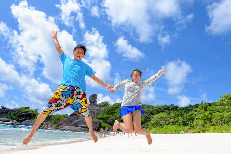 Fader- och dotterbanhoppning på stranden på Thailand royaltyfri fotografi