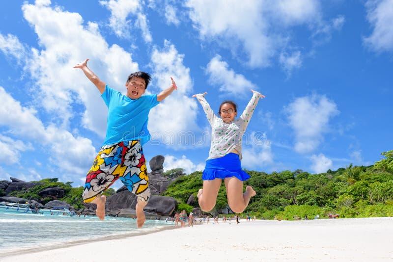 Fader- och dotterbanhoppning på stranden på Thailand royaltyfri foto