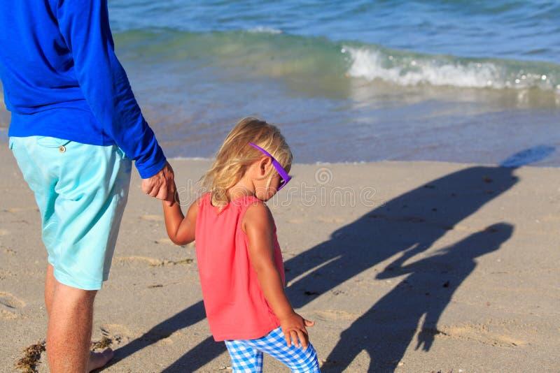 Fader- och dotterinnehavhänder på stranden med skugga på sand royaltyfri bild