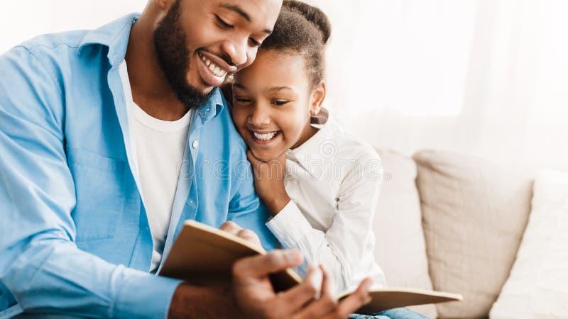 Fader- och dotterläsebok tillsammans hemma arkivfoton